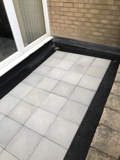 A fully tiled balcony outside patio windows