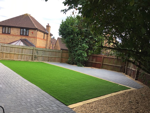 An artificial lawn laid in a rectangle with block pave patios on either side