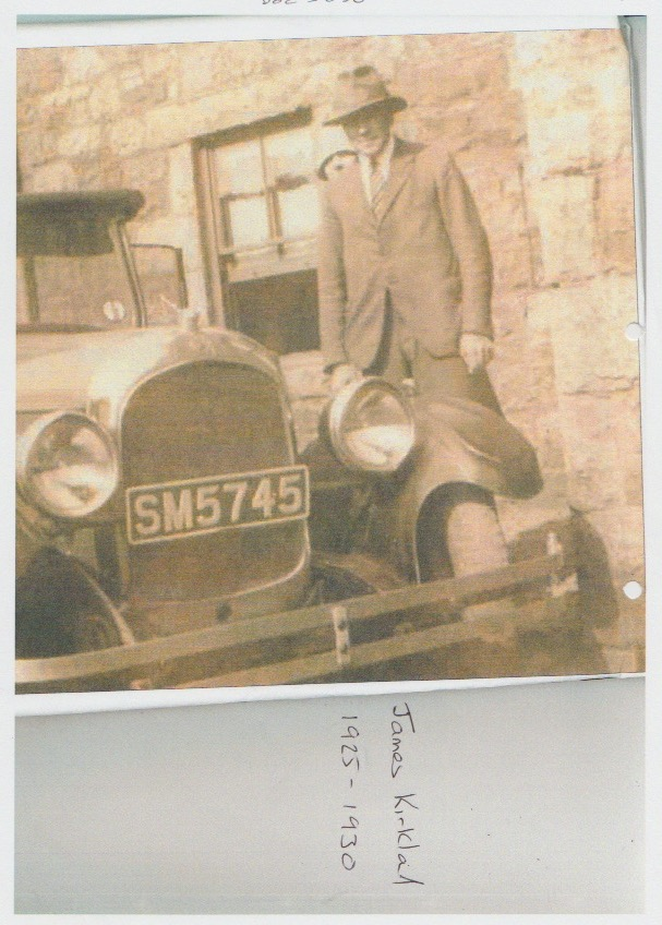 James Kirkland standing in front of a motor car bearing the number SM5745