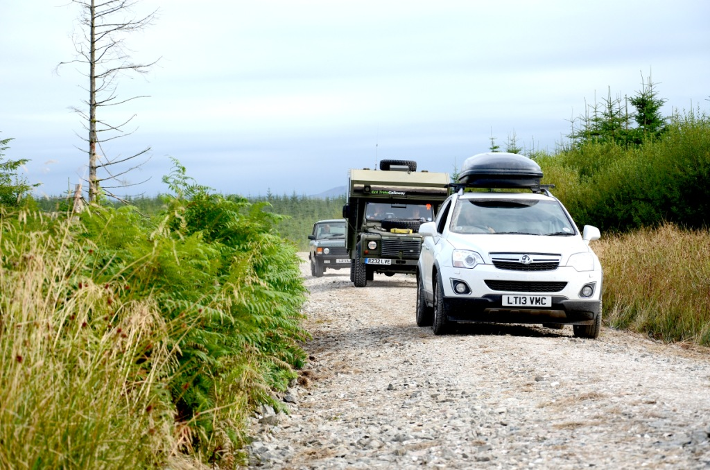 Three 4x4 vehicles off road in a Scottish forest