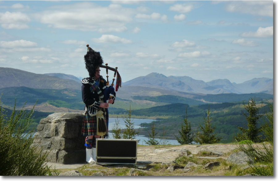 A Highland piper in traditional outfit playing near Loch Ness