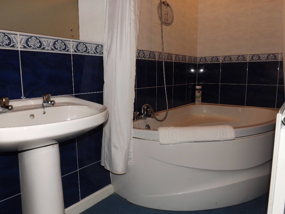 Portpatrick self catering holidays - A bathroom with corner bath at Braefield House, Portpatrick