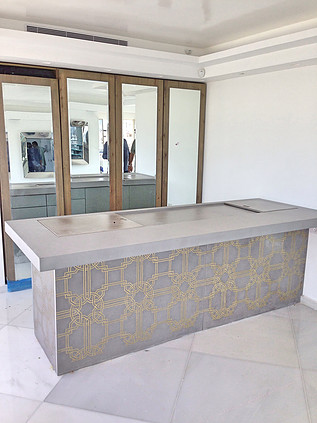 A kitchen counter fronted with gold-patterned tiles