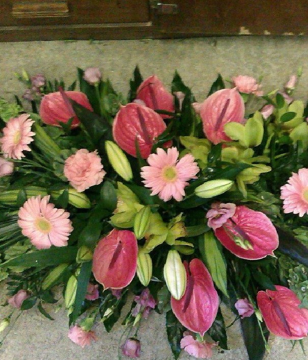 A funeral wreath from Flowers for You, Dalbeattie, using a mixture of green foliage, pink crysanthemums and pink calla lilies
