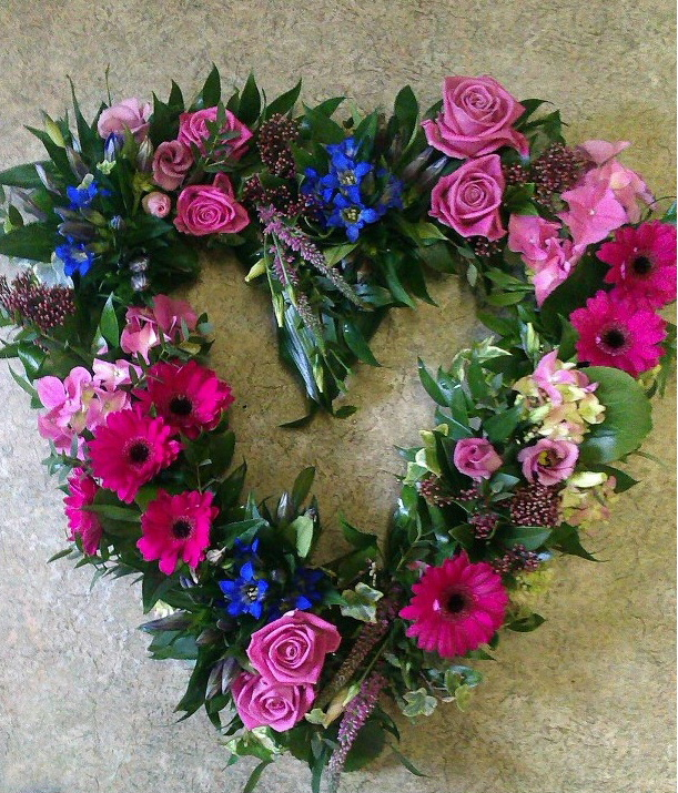 A funeral wreath from Flowers for You, Dalbeattie, using a large selection of flowers in varied colours, in a heart shape