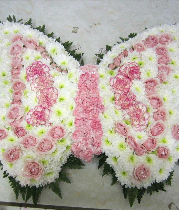 A funeral wreath from Flowers for You, Dalbeattie, using pink roses and white chrysanthemums in the shape of a beautiful butterfly
