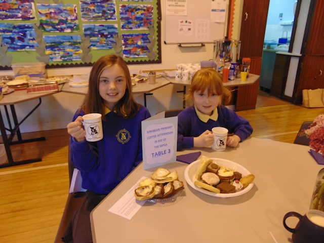 Two young schoolgirls with mugs in front of a table laden with cakes and biscuits