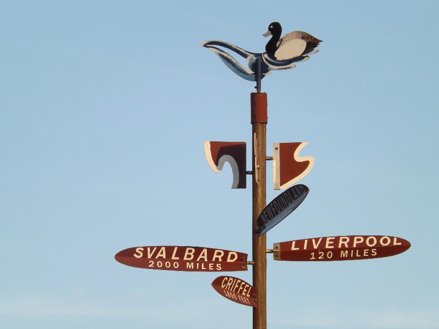 A finger post sign with distances to Svalbard, Liverpool and the Criffel at Carsethorn in Dumfries and Galloway, Scotland Kirkbean.org
