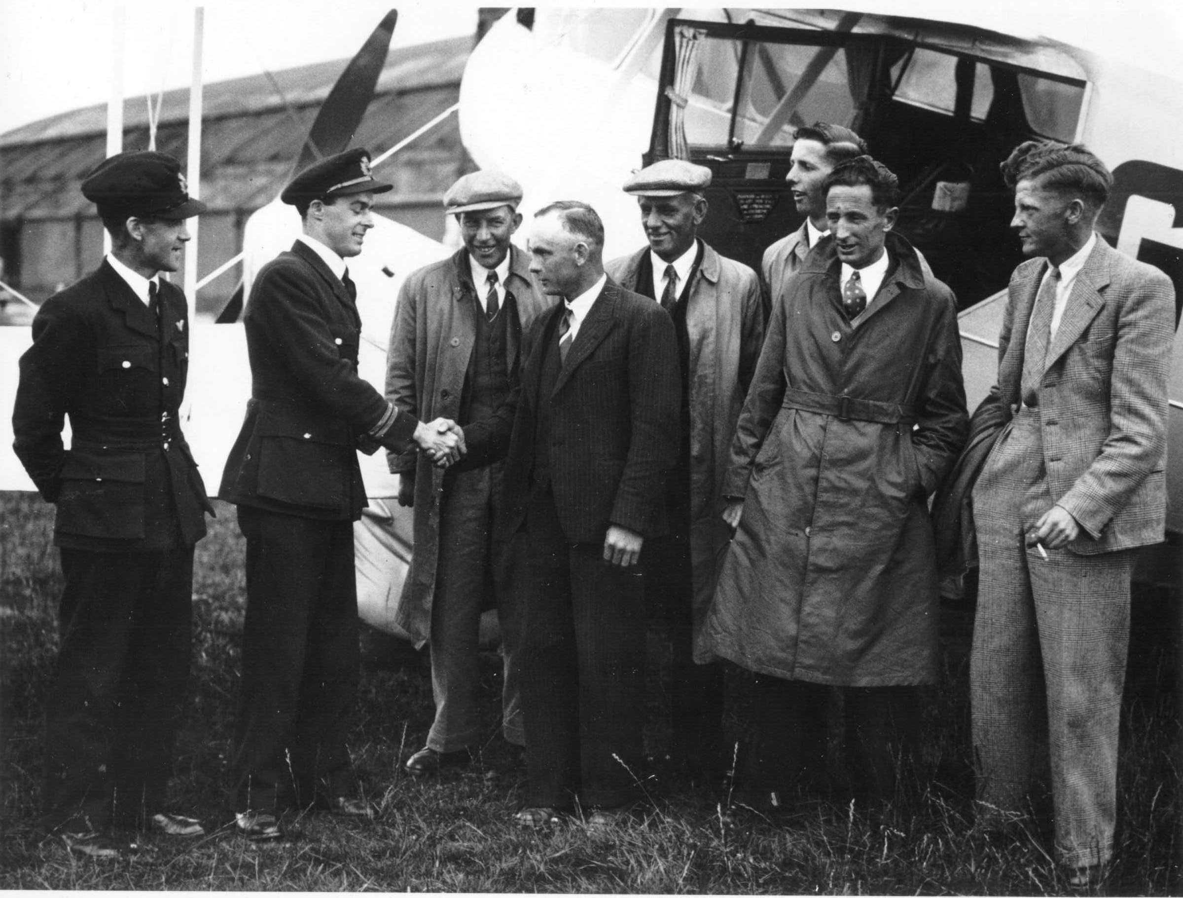 Two fligth crew with a group of local men in front of an aeroplane