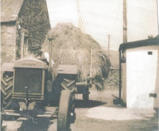 tractor with haystack in a farmyard