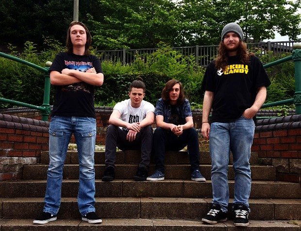 Rock band Revival members pictured sitting on steps in a park