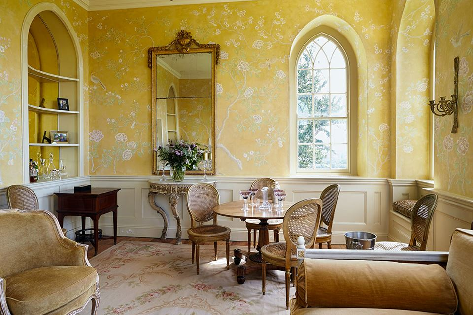 Chinoiserie-gold walls with chinese flowers and birds in room with gothic arch windows.