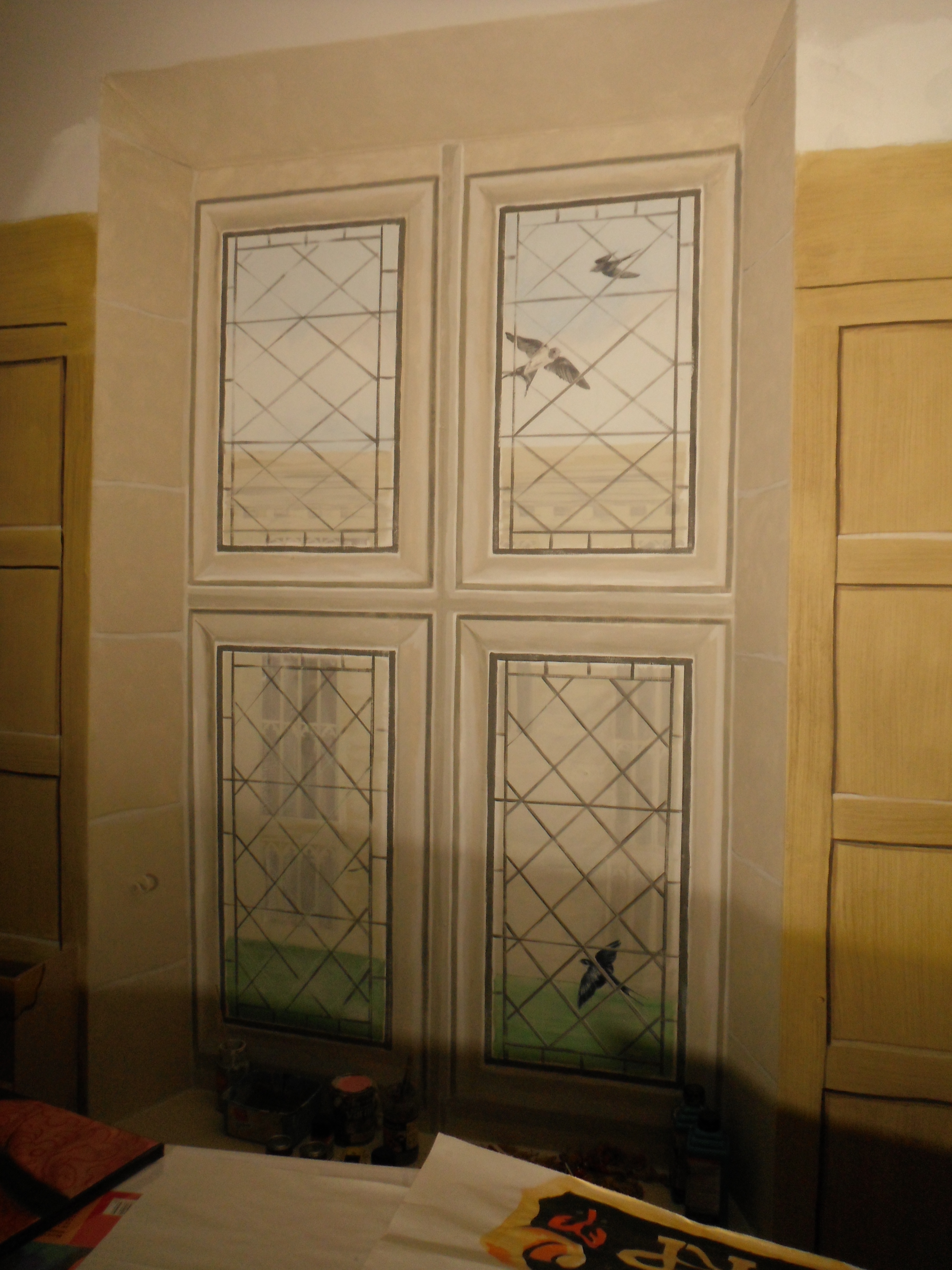 Trompe l'oeil- old leaded window with fake stone surround. Looking out onto a courtyar; Window with swallows flying past.