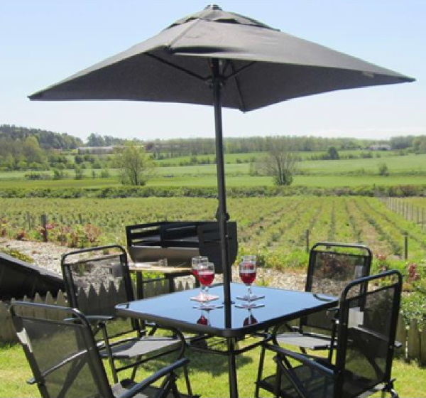 Relaxation and Tranquility in this rural scene with table and chairs under a parasol in the garden look out over acres of green countryside