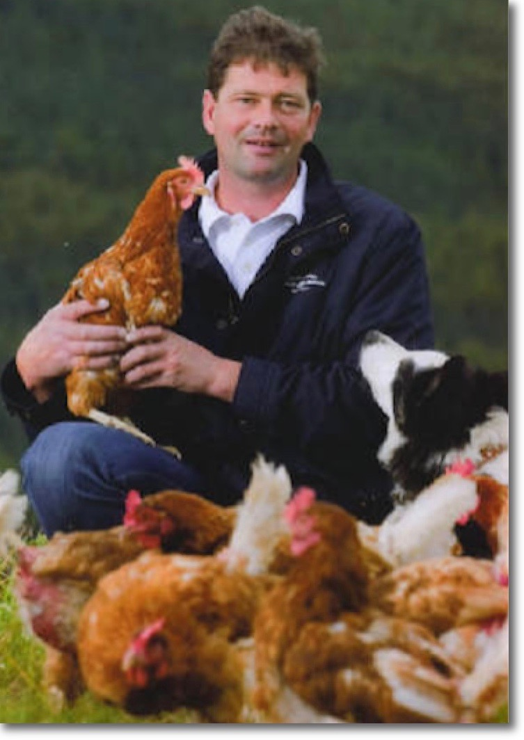 Owner Bruce McMyn surrounded by his Lohmann hens and a collie dog