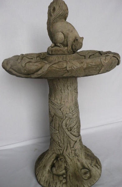 Bird bath with a squirrel on top