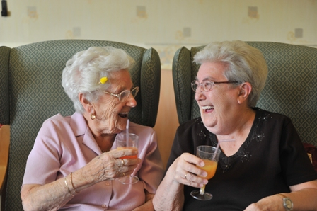 Two ladies enjoying a glass of orange juice