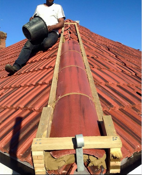 The Roofing Co Ltd workman having completed the retiling of an old roof, displaying the roofline tiling