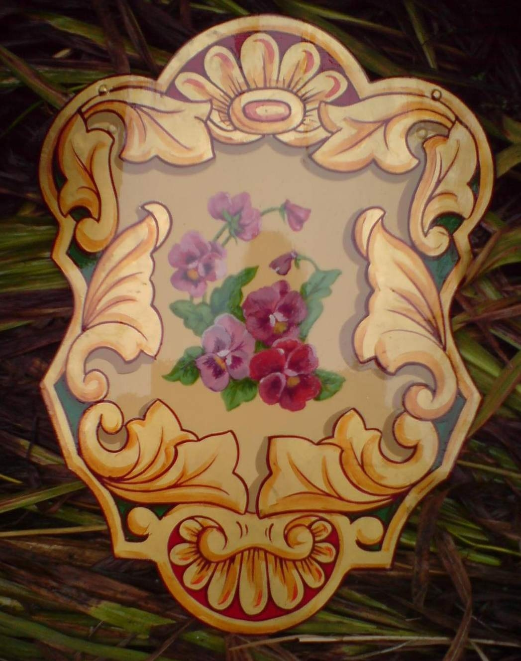 Fairground painting. Shield with gold leaf scrolls on edges with purple pansies in centre.