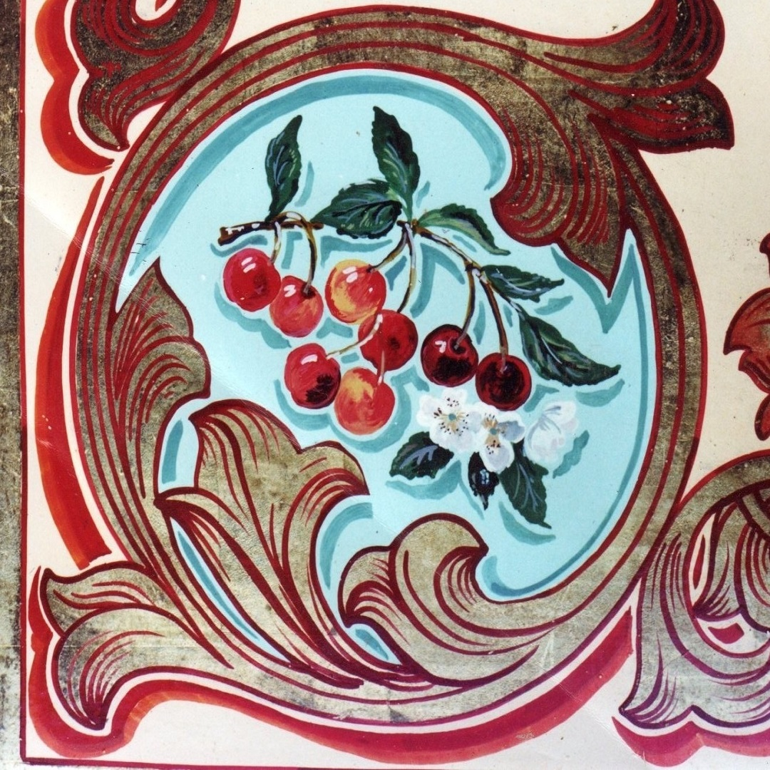 A corner of a painted panel for a showmans wagon. Gold leaf  scroll with painted cherries andlossom on a turquois background.