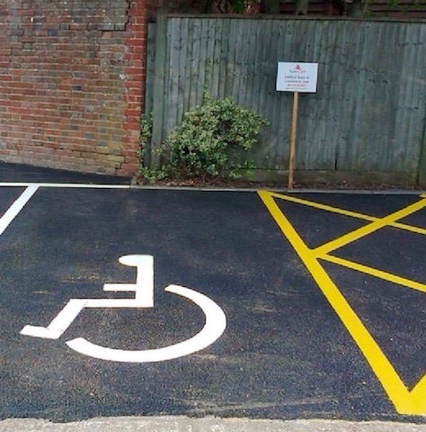 Yellow line markings and disabled bay markings in a car parking space