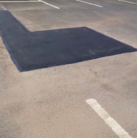 Section of a car park where a pothole has been filled in with tar macadam