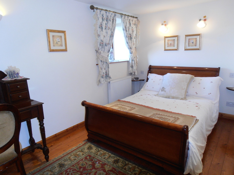 A double bed and other classic furniture adorn this beautiful double bedroom within The Dairy House self-catering holiday accommodation near Kirkcudbright