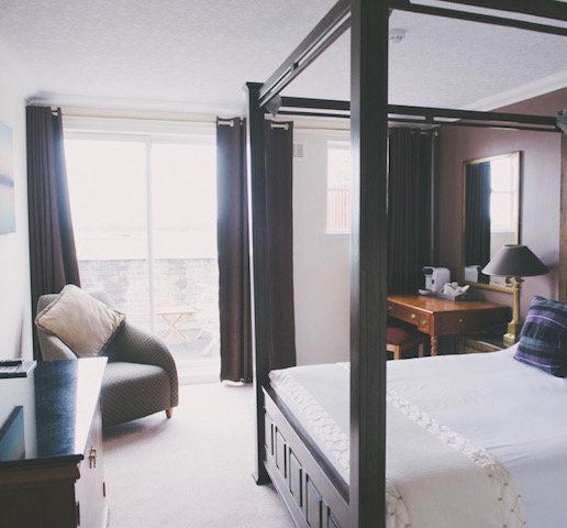 A spacious bedroom at The Powfoot Hotel with four-poster bed