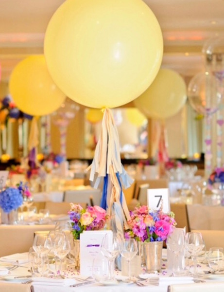 A wedding breakfast decorate table with yellow balloons with colourful ribbons tied to their strings