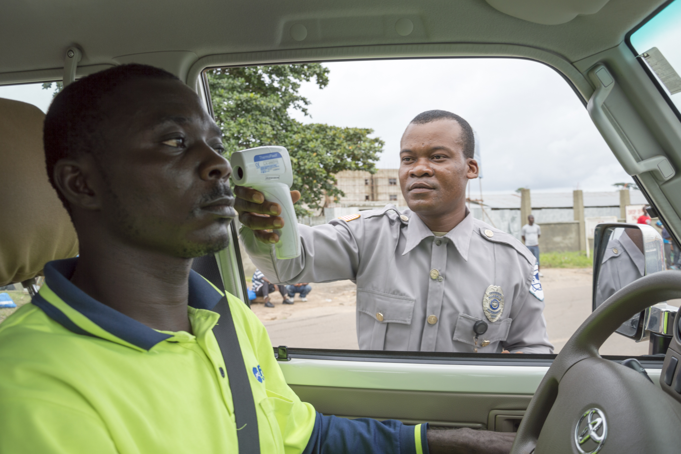 A policeman in Liberia takes temperatures at a checkpoint