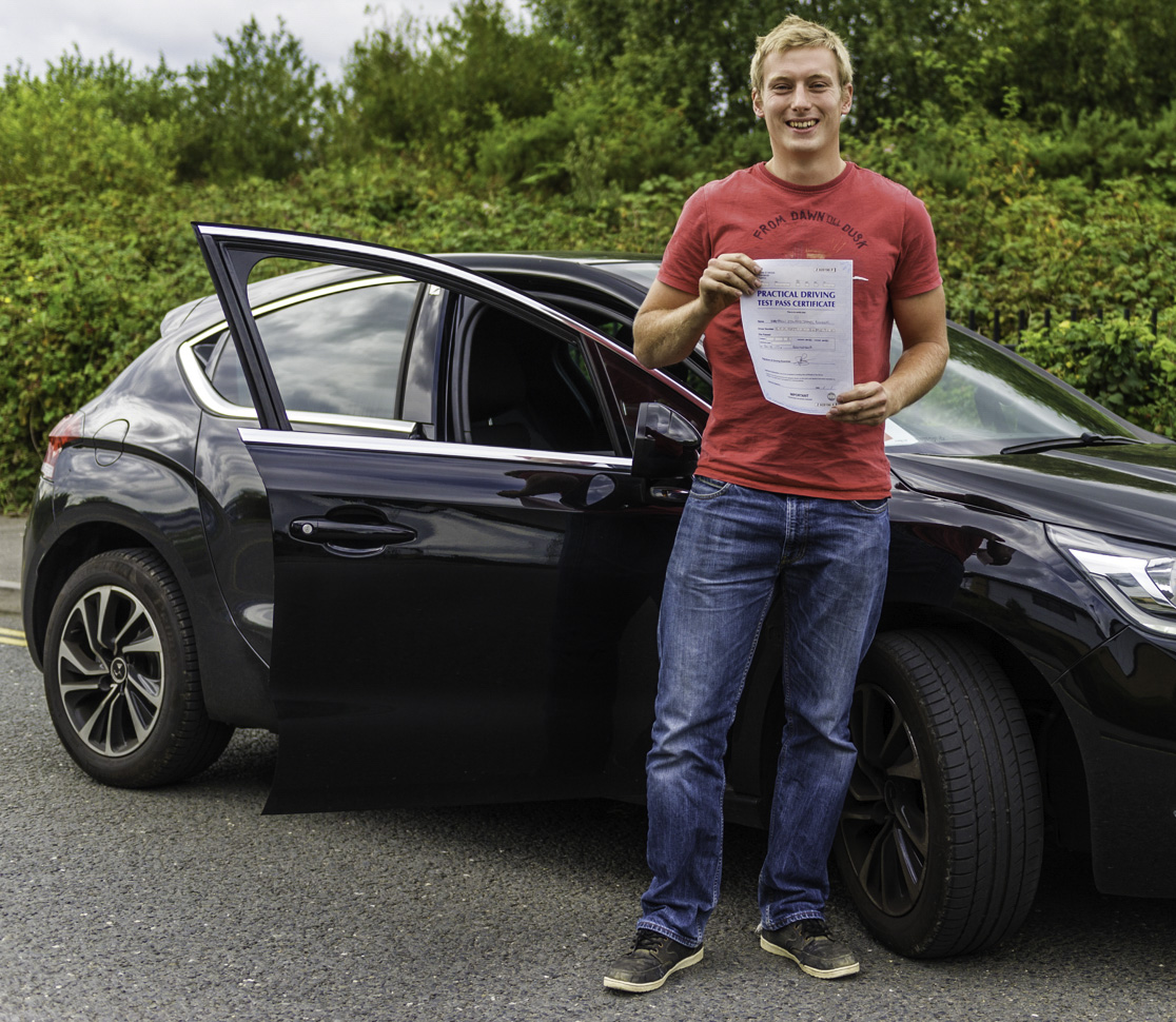 Young man standing next to black car holding blue driving test pass certificate