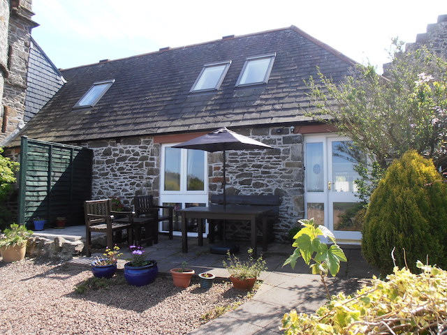The Dairy Cottage has a private patio area with garden furniture, surrounded by greenery
