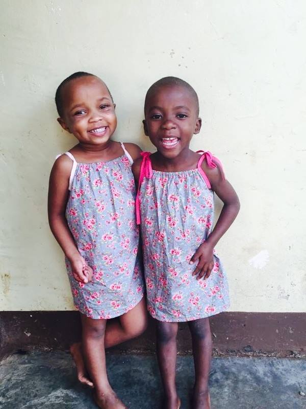 Two very happy girls in Africa wearing dresses I've made!