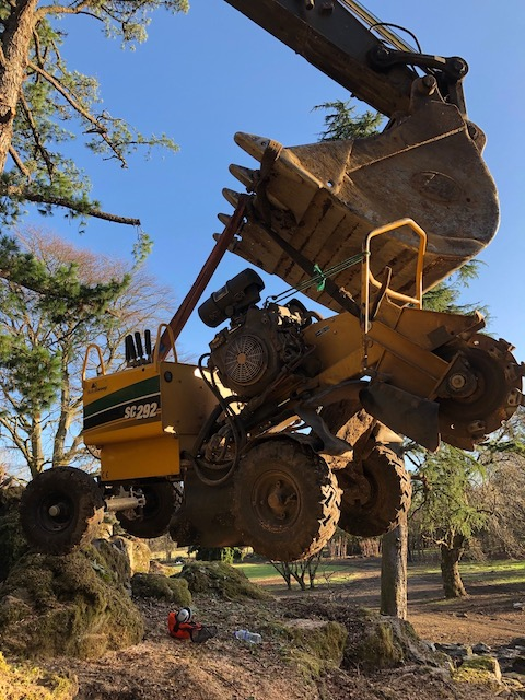 Stump grinding equipment being lowered into position