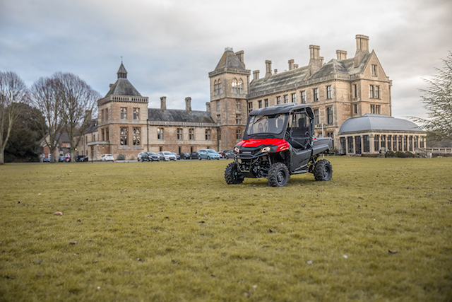 Red Honda Pioneer ATV with cab outside a stately home