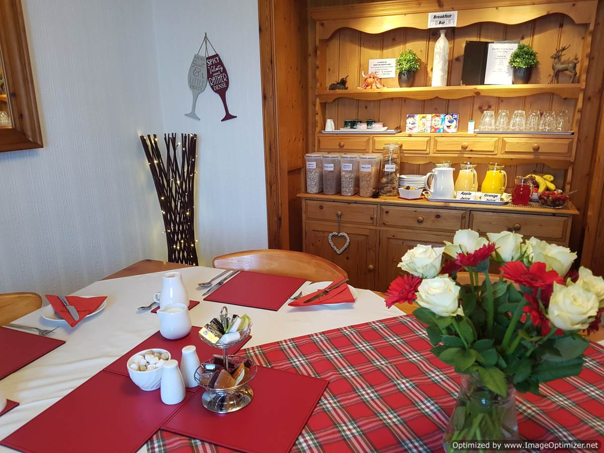 The beautifully presented breakfast table and welcoming breakfast bar laden with fruit juices, fresh fruit and cereals