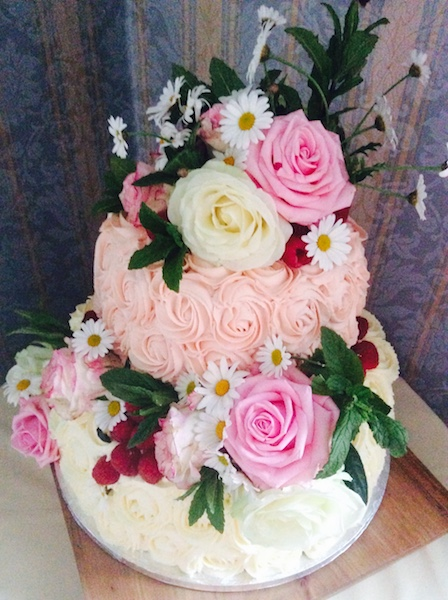 A gorgeous wedding cake with piped icing roses and real roses and Michaelmas daisies
