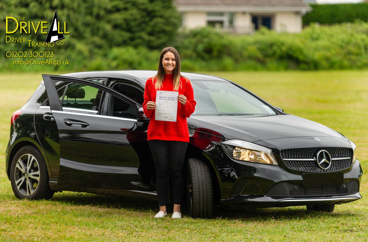 Young woman standing next to black car holding blue driving test pass certificate