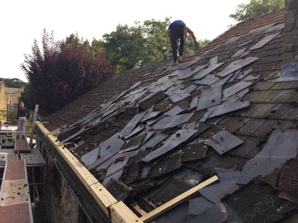 Workman on roof removing old tiles from a house in Kilwinning