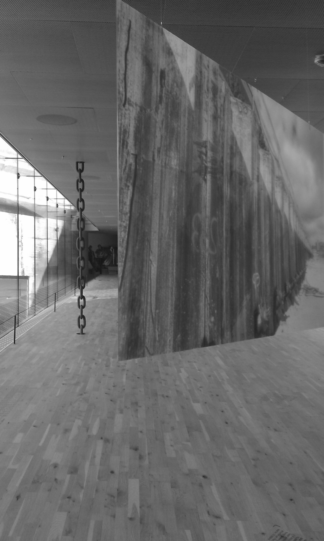 Greyscale image of glass walls, wood, concrete and chain