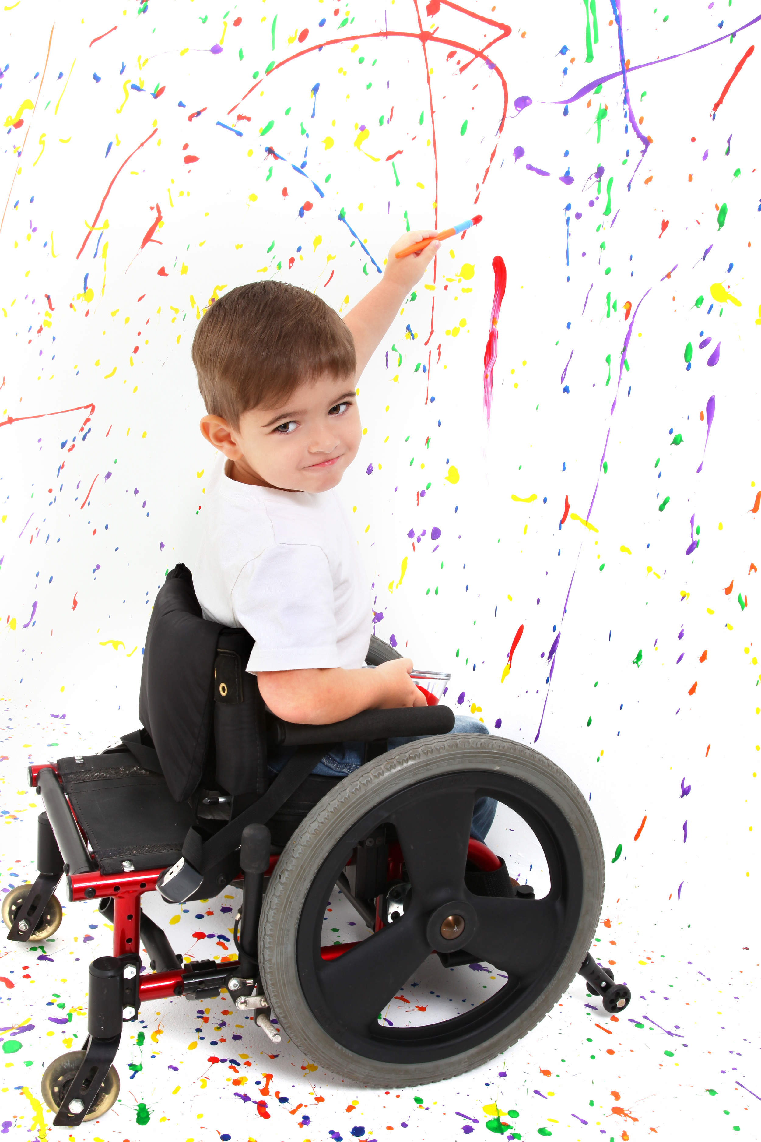 Young boy in a wheelchair painting the wall