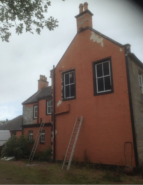 Gable end of a large house with peeling orange paint