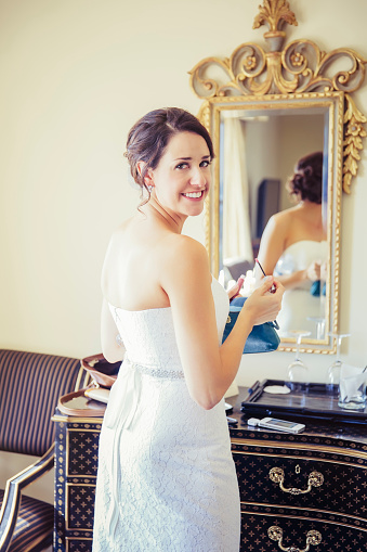 caucasian-bride-applying-makeup-in-mirror-picture-id591406965jpg