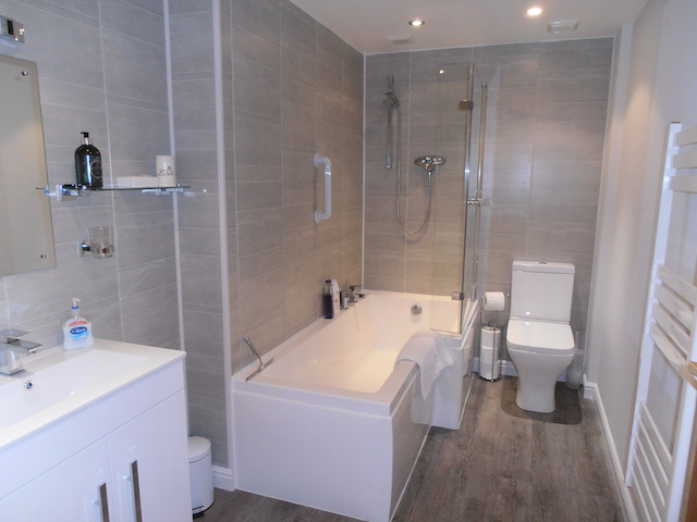 Sleek and stunning new bathroom with bath and shower over, grab rails and ladder radiator