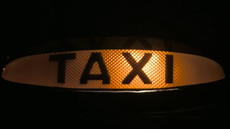 the illuminated sign of a black taxi from Paul Olding's short film Taxi