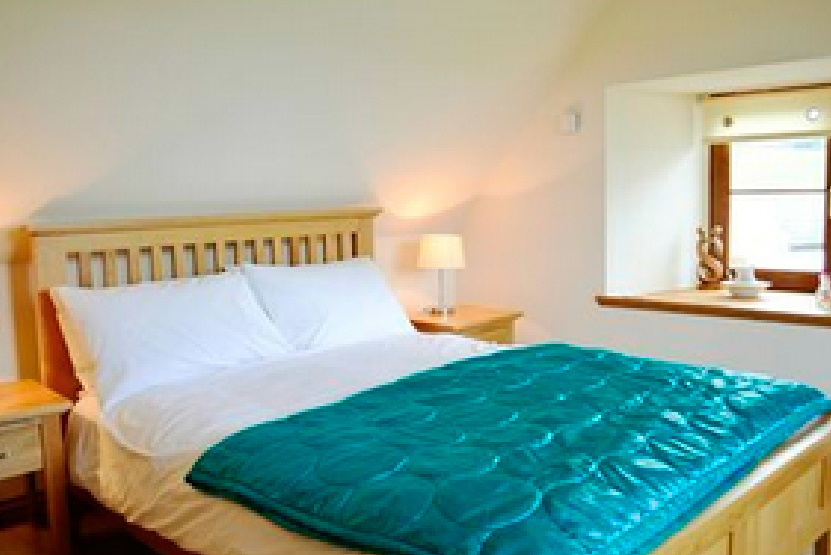 King size bed at Drumfad Holiday Cottage, Port William, Dumfries and Galloway, Scotland