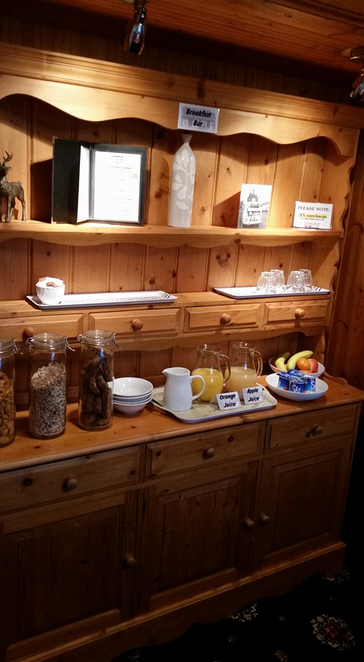 The breakfast buffet bar with orange and apple juice, fresh fruit and cereals