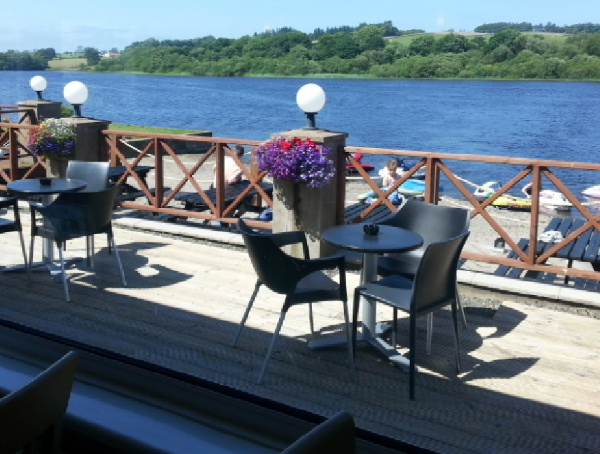 Bistro style seating area on decking overlooking the loch