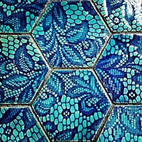 A hexagonal blue patterned tile designed by the Guy Mitchell tile studio
