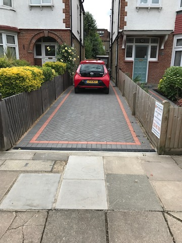 Making better use of old pathway by laying block paving for use as a driveway, including red tiles marking out safe area to park